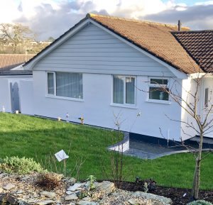 Front gable cladded in cedral and house painted in white