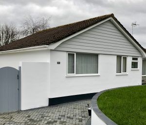 House painted white with slate grey garden gate and anthracite grey plinths